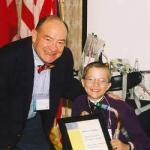 Mattie presenting Jim Hawkins with the Mattie J.T. Stepanek Champion Award during a September 2003 CHI conference. Hawkins has volunteered as a photographer for CHI, capturing many of the events and activities of the organization. He also became a close friend to Mattie and his mom, Jeni.